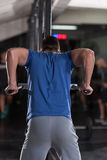 Man doing exercises parallel bars. Young muscular bodybuilder working out in gym doing exercises parallel bars  Concept sport Royalty Free Stock Photo