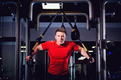 A man is doing exercises on  simulator in the gym Royalty Free Stock Photography