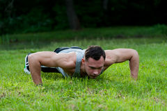 Man doing fitness exercise on the grass Stock Photo