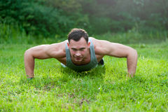 Man doing fitness exercise on the grass Stock Images