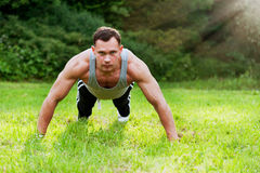 Man doing fitness exercise on the grass Stock Photos