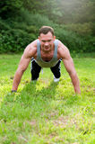 Man doing fitness exercise on the grass Stock Image