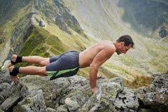 Man doing fitness on a mountain Stock Photos