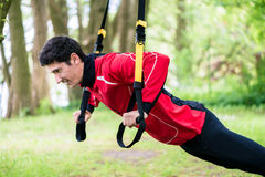 Man doing fitness sling training outdoors Stock Photos