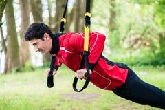 Man doing fitness sling training outdoors Stock Photos