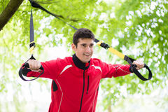Man doing fitness sling training outdoors royalty free stock photography