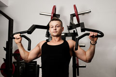 Man doing fitness training. On machine with weights in a gym Stock Image