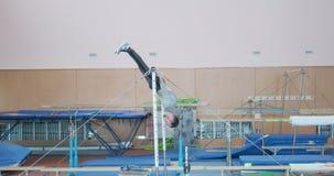 Man doing gymnastics on bar. Athletic man doing gymnastics on horizontal bar at gym stock video
