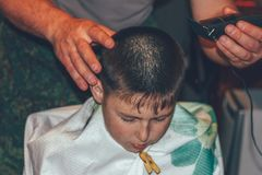 Man doing a haircut boy teenager. Electric machine Royalty Free Stock Images