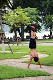 Man doing a hand stand in Lenin Park, Hanoi, Vietnam. With red trainers Royalty Free Stock Photos
