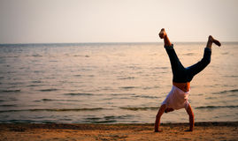 Man doing handstand on beach Stock Photos