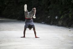 Man doing handstand and walking on street, Jamaica. Young artistic man doing hand stand, Ocho Rios, Jamaica stock photos