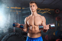 Man doing heavy weight exercise with dumbbells in gym Stock Image