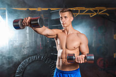 Man doing heavy weight exercise with dumbbells in gym Stock Images