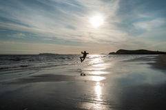 A man doing a heel click jump on the left side at the beach Stock Photos