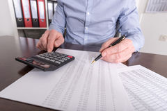 Man doing his accounting. Man with calculator doing his accounting Royalty Free Stock Photo