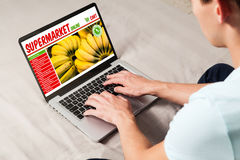 Man doing his grocery shopping by internet with a laptop at home Royalty Free Stock Image