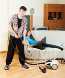 Man doing house cleaning during girl resting Stock Photography