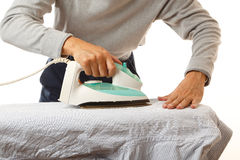 Man doing housework. An Asian man doing housework, ironing shirt, on white background stock image