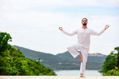 Man Doing Indian classic Yoga at the Sea and Mountains Stock Images