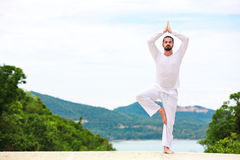 Man Doing Indian classic Yoga at the Sea and Mountains Royalty Free Stock Photo