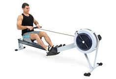 Man doing indoor rowing. Man exercising on rowing machine,  hands slightly blurred in motion Royalty Free Stock Photography