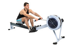 Man doing indoor rowing. Man exercising on rowing machine,  hands slightly blurred in motion Stock Image