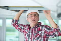 Man doing installation air conditioner and heating duct. Man doing an installation of air conditioner and heating duct stock photo
