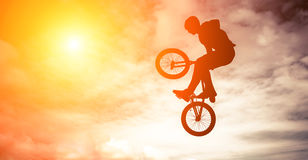 Man doing an jump with a bike. Silhouette of a man doing an jump with a bmx bike against sunshine sky Stock Images