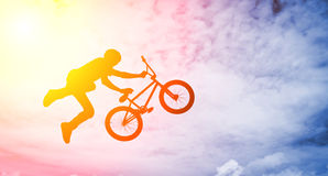 Man doing an jump with a bmx bike . Silhouette of a man doing an jump with a bmx bike against sunshine sky Royalty Free Stock Photos