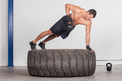 Man doing kettlebell training on a tire crossfit Stock Images