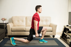 Man doing kneeling lunges with weights Royalty Free Stock Photos