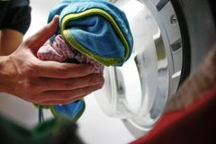 Man doing laundry in laundromat, view from the inside of washing. Machine stock photography