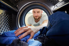 Man Doing Laundry Reaching Inside Washing Machine stock photography
