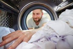 Man Doing Laundry Reaching Inside Washing Machine Stock Image