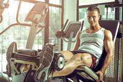 Man doing leg extension in gym Stock Images
