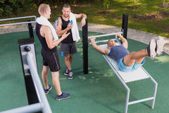 Man doing leg lifts. At outdoor gym Royalty Free Stock Photography