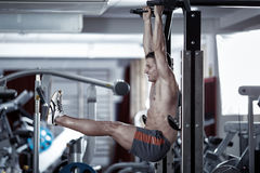 Man doing leg raises. Athletic man doing abs crunches from hanging position Stock Images