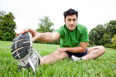 Man doing leg stretches in the park Royalty Free Stock Photos