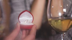 Man doing marriage proposal to woman in restaurant closeup. Man doing marriage proposal to woman in restaurant, closeup of box with engagement ring stock footage