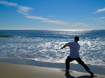 Man doing martial arts on beautiful beach Royalty Free Stock Image