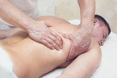 Man doing massage. Man doing sports massage at the massage parlor Stock Images