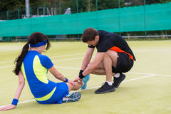 Man doing massage to his female tennis partner. After  tennis match on a court outdoor in summer or spring Stock Photos