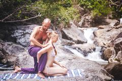 A man is doing a massage for a woman in the nature next to a wat. A men is doing a massage for a women in the nature next to a waterfall. Beauty, nature, health Stock Photos