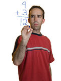 Man Doing Math. A young man doing simple math with a marker stock photography