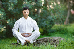 Man doing meditation sitting on the stone outdoors Stock Images