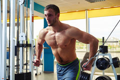 Man doing muscles workout on cable crossover machine Stock Photography