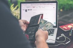 Man doing online shopping with credit card, laptop and luxury snakeskin python wallet. Man online shopping concept. royalty free stock photography
