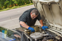 Man doing own car repair on the road Stock Photo