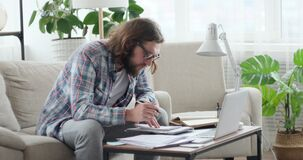 Man doing paperwork and using laptop at home office